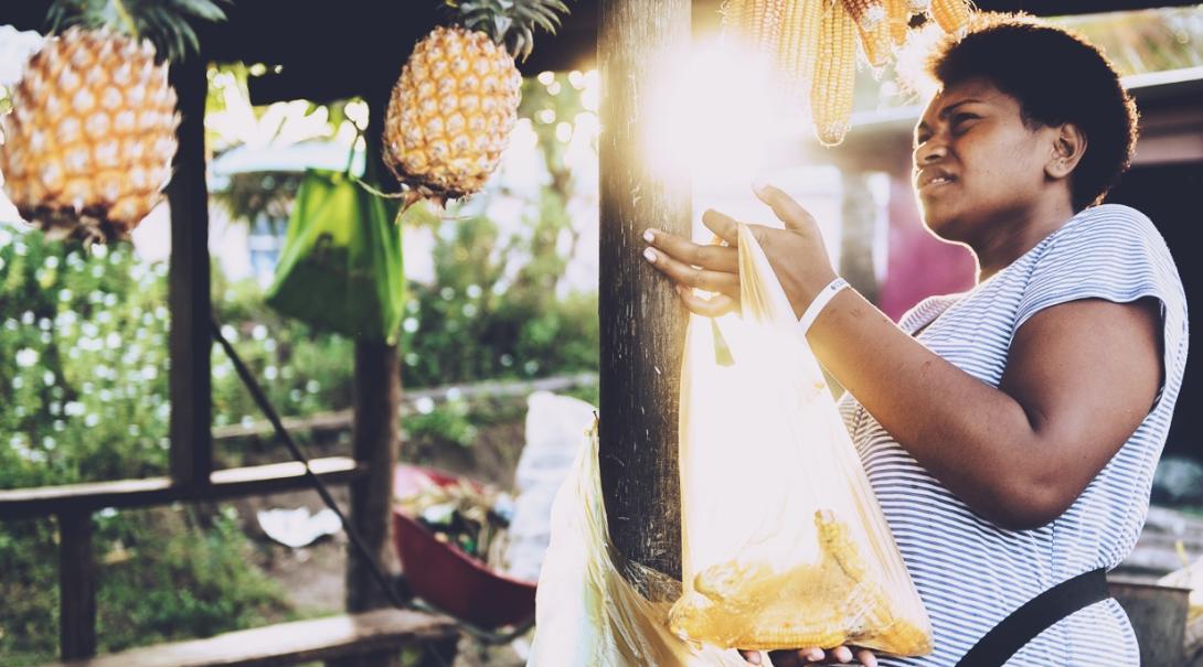 トウモロコシを袋に詰めるフィジー女性